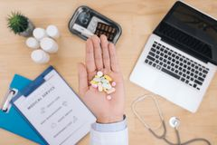Male doctor hand holding different colorful capsule. Medical treatment, antibiotics resistance problem and rational drug use. Concept. Selective focus royalty free stock image