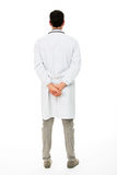 Male doctor with hands behind his back. Full length backside view of a male doctor with hands behind his back Royalty Free Stock Photo