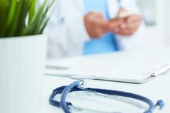 Blue stethoscope lies on the table in the foreground and male doctor hands texting on a smart phone in background. royalty free stock image