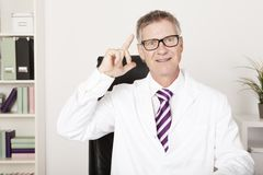 Male doctor having a brainwave. Middle-aged male doctor working in his office having a brainwave or breakthrough idea as he raises his finger with a happy smile Royalty Free Stock Images