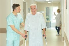Male doctor helping old man with crutches. Male doctor is helping old men with crutches Stock Photography