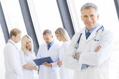 Male doctor and her team. Successful mature male doctor and his team on background in clinical office Stock Images