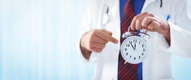 Male doctor holding an alarm clock Stock Photos