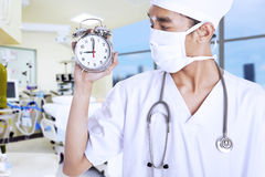 A male doctor holding an alarm clock Stock Photo