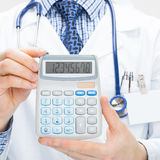 Male doctor holding calculator in hands - health care concept Royalty Free Stock Image