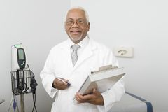 Male Doctor Holding Clipboard At Clinic Stock Image