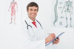 Male doctor holding clipboard in the medical office Stock Photos