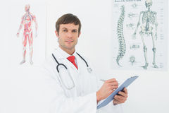 Male doctor holding clipboard in the medical office Stock Photography