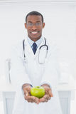 Male doctor holding a green apple at medical office Stock Photos