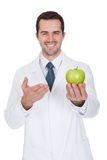 Male Doctor Holding Green Apple Stock Image