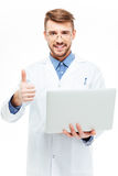 Male doctor holding laptop computer and showing thumb up Royalty Free Stock Photography