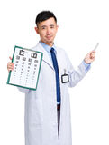 Male doctor holding optometry chart and pen pointing up Stock Image