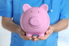 Male doctor holding piggy bank, close up. Concept of medical insurance Stock Photography
