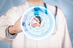 Male doctor holding a pill with glowing circles Royalty Free Stock Images
