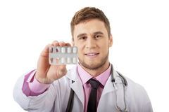 Male doctor holding pills. Royalty Free Stock Images