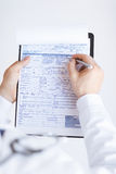 Male doctor holding prescription paper in hand Royalty Free Stock Photo