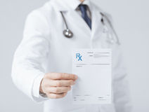 Male doctor holding rx paper in hand Royalty Free Stock Photography