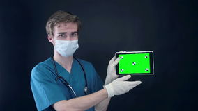 Male doctor holding, showing digital tablet with green screen. stock video footage