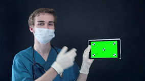 Male doctor holding, showing digital tablet with green screen. stock video