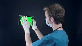 Male doctor holding, showing digital tablet with green screen. stock footage