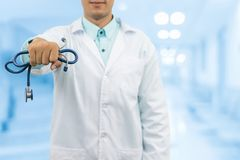 Male doctor holding stethoscope in the hospital. Male doctor holding stethoscope, smiling on hospital background. Healthcare service, general practice and Royalty Free Stock Image