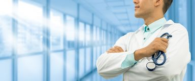 Male doctor holding stethoscope in the hospital. Male doctor holding stethoscope, smiling on hospital background. Healthcare service, general practice and Royalty Free Stock Photos