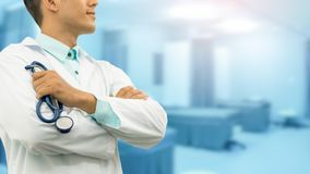 Male doctor holding stethoscope in the hospital. Male doctor holding stethoscope, smiling on hospital background. Healthcare service, general practice and Stock Image