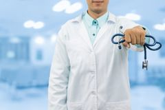 Male doctor holding stethoscope in the hospital. Male doctor holding stethoscope, smiling on hospital background. Healthcare service, general practice and Stock Photography