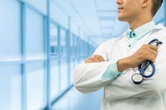 Male doctor holding stethoscope in the hospital. Male doctor holding stethoscope, smiling on hospital background. Healthcare service, general practice and Royalty Free Stock Photo