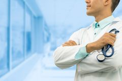 Male doctor holding stethoscope in the hospital. Male doctor holding stethoscope, smiling on hospital background. Healthcare service, general practice and Royalty Free Stock Photography