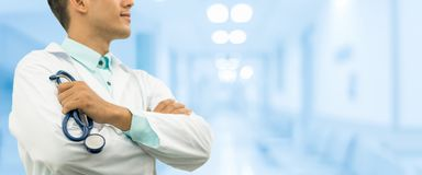 Male doctor holding stethoscope in the hospital. Male doctor holding stethoscope, smiling on hospital background. Healthcare service, general practice and Stock Images