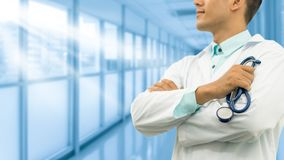 Male doctor holding stethoscope in the hospital. Male doctor holding stethoscope, smiling on hospital background. Healthcare service, general practice and Stock Photo