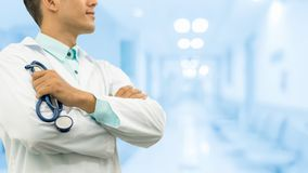 Male doctor holding stethoscope in the hospital. Male doctor holding stethoscope, smiling on hospital background. Healthcare service, general practice and Royalty Free Stock Images