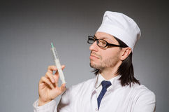 The male doctor holding syringe against gray Stock Photography