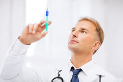 Male doctor holding syringe with injection Royalty Free Stock Images