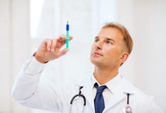 Male doctor holding syringe with injection Stock Images