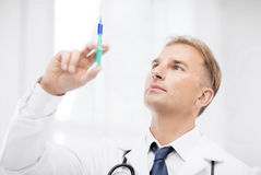 Male doctor holding syringe with injection Stock Photo