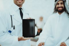 Male Doctor Holding Tablet Arabic Man at Hospital royalty free stock photos