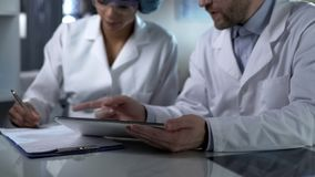 Male doctor holding tablet, giving female assistant instructions to note down stock images