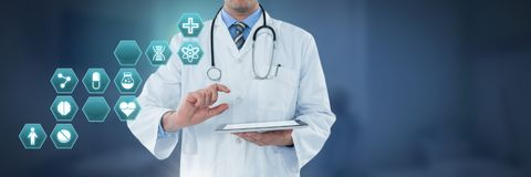 Male doctor holding tablet with medical interface hexagon icons stock image