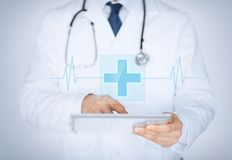 Male doctor holding tablet pc with medical app. Close up of male doctor holding tablet pc with medical app stock photography