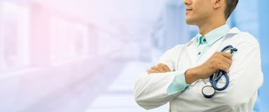 Male Doctor on Hospital Background. Male doctor holding stethoscope, smiling on hospital background. Healthcare service, general practice doctor and medical Stock Photo