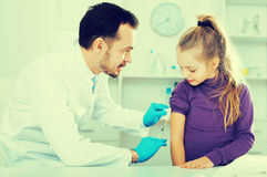 Male doctor injecting little patient Royalty Free Stock Photo