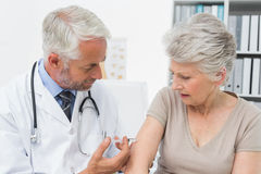 Male doctor injecting senior female patient Royalty Free Stock Photo
