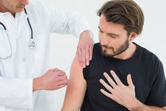 Male doctor injecting a young male patients arm Stock Images