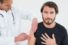 Male doctor injecting a young male patients arm Stock Photos