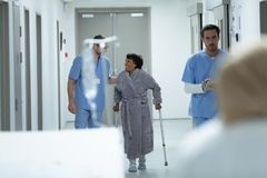 Male doctor interacting with disabled female patient in the corridor stock photos