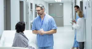 Male doctor interacting with disabled female patient in the corridor stock photography