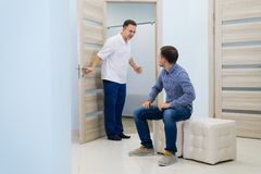 Male doctor inviting male patient to his office royalty free stock image