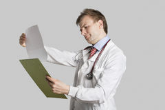 Male doctor in a lab coat reading medical records over gray background Stock Photo